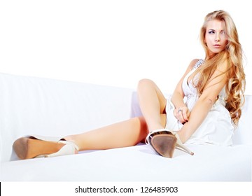 Beautiful young woman with magnificent blonde hair sitting on a sofa. Isolated over white.