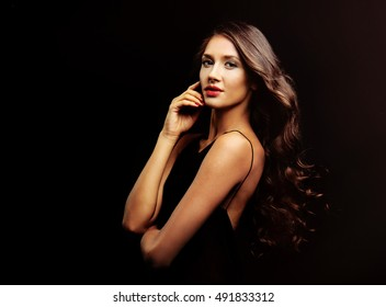 Beautiful young woman with make up and long  wavy hair on black background