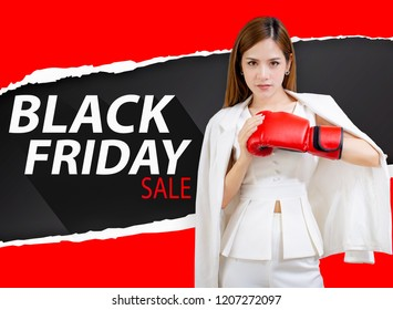 Beautiful young woman make shopping in black friday holiday. Girl with red boxing gloves on dark background design.