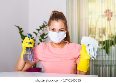 Beautiful young woman makes cleaning the house. Girl rubs dust. Woman in protective gloves and mask is wiping dust using a spray and a duster while cleaning her house, close-up