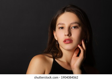 beautiful young woman with makeup on black background