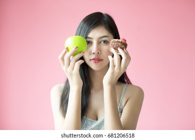 Beautiful young woman making a choice between a cake and apple