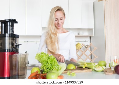 Beautiful young woman making fresg juice from vegetables and salad. Cooking concept of happy family. Squeezing maching, slow juicer on home kitchen.