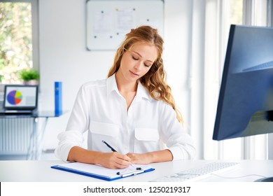 Beautiful young woman making notes while sitting at office desk in front of computer and working.