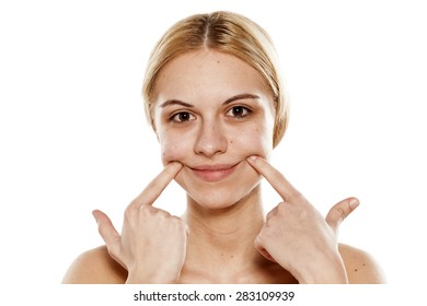 Beautiful young woman making a smile with her fingers