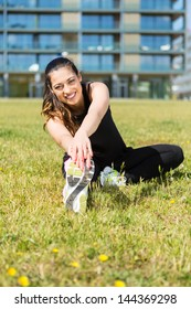 A beautiful young woman making some exercise at the park - fitness concept