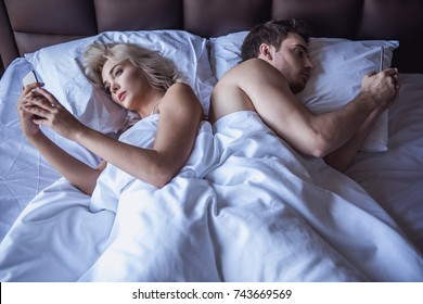 Beautiful young woman and man are using their smart phones while lying back to back in bed at home