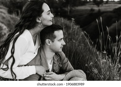 Beautiful young woman and a man walk, hug and kiss in nature at sunset.