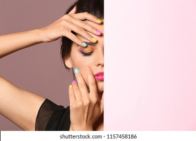 Beautiful young woman with beautiful manicure and blank poster on color background
