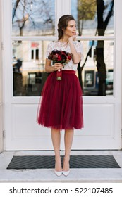 249c712f5 Beautiful young woman in marsala tulle skirt on heels walking on street. She  holds bouquet