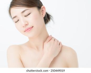 Beautiful young woman massaging her shoulder