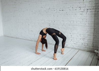 "A beautiful young woman, meaning ""Wild kitty"", works in the fitness club or at home, doing yoga or Pilates exercises. Advanced bridge pose, chakrasana. Full length"