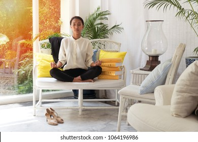 Beautiful young woman meditates on a long white chair in living room with a stack of colored books left beside her in living room. Businesswoman practicing yoga at home.Relax after work concept