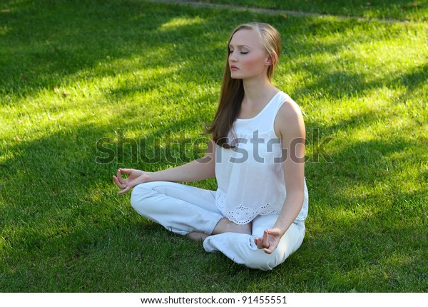 Beautiful young woman meditating in a garden