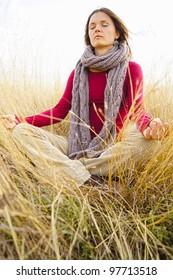 Beautiful young woman meditating in long grass field