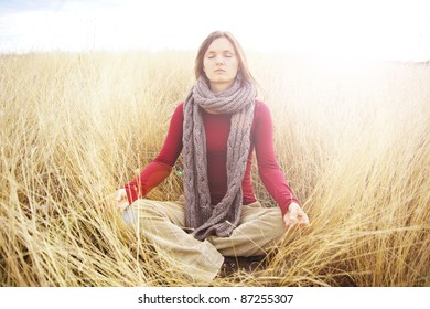 Beautiful young woman meditating in a open field in the long autumn grass