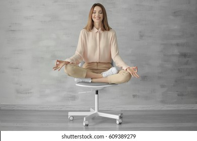 Beautiful young woman meditating while sitting on chair indoors