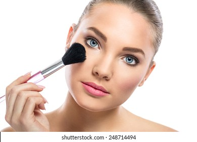 Beautiful young woman with mirror applying powder on cheek