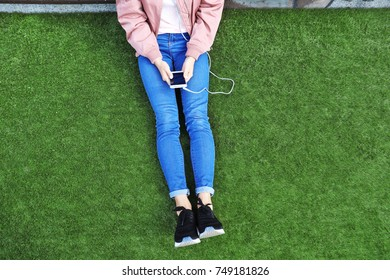 Beautiful young woman with mobile phone listening to music outdoors