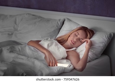 Beautiful young woman with mobile phone sleeping in bed