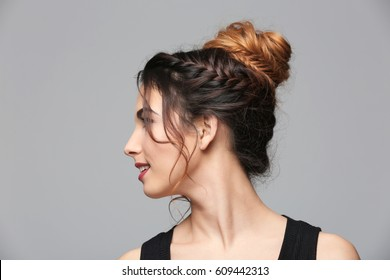 Beautiful young woman with modern hairstyle on grey background