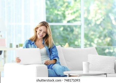 Beautiful young woman with modern laptop on sofa at home