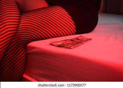 Beautiful young woman with money in a red light, sign of prostitution.
