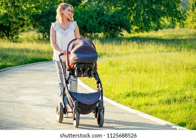 beautiful and young woman mother and baby in a stroller walking in the park