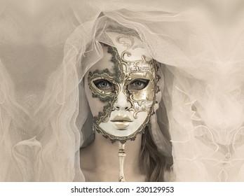Beautiful young woman in mysterious golden Venetian mask.