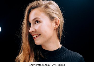 beautiful young woman mysteriously looks on a black background