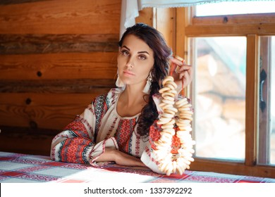 beautiful young woman in national costume sitting in a hut