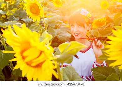 Beautiful young woman in national ukrainian blouse embrodery looking to camera on a sunflower field at sunset, backlight.