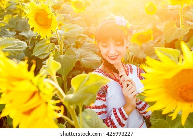 Beautiful young woman in national ukrainian blouse embrodery with closed eyes on a sunflower field at sunset, backlight.