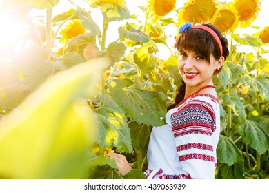 Beautiful young woman in national ukrainian blouse embrodery looking to camera on a sunflower plant at sunset, backlight.