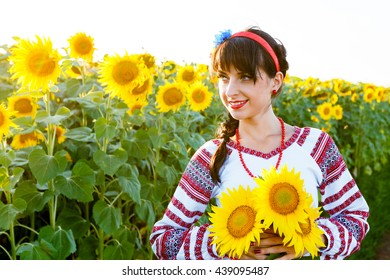 Beautiful young woman in national ukrainian blouse embrodery holding three sunflowers on a plant at sunset, backlight.