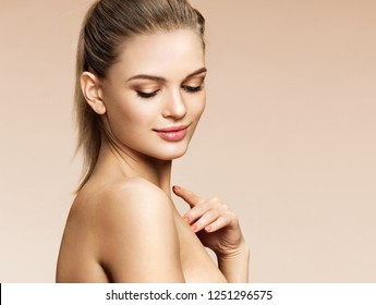 Beautiful young woman with natural nude make up and touching her face on beige background. Beauty & Skin care concept