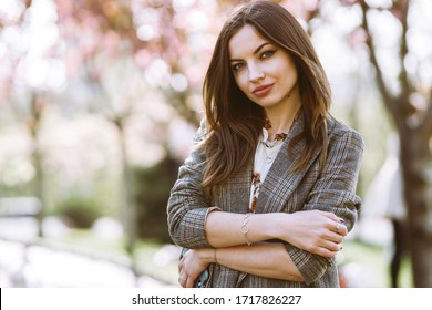 Beautiful young woman near the blooming spring tree. Attractive girl enjoying her time outside in park. Spring time.