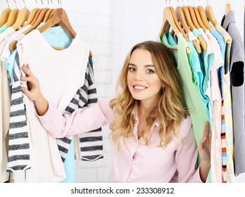 Beautiful young woman near rack with hangers