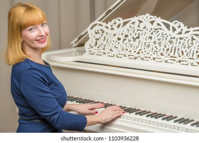 Beautiful young woman near a white grand piano. The concept of musical education, creative development of personality.