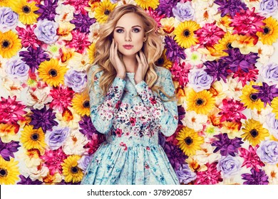 Beautiful young woman in nice blue dress posing on colorful wall of flowers. Fashion photo, nice hair, big smile