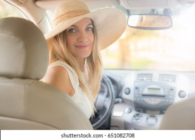 beautiful young woman in the nice car is going to vacation to the beach
