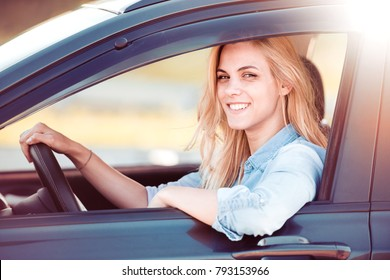 Beautiful young woman in the nice car is going to vacation.