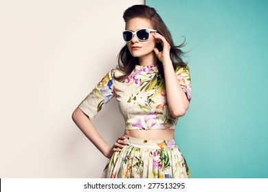 beautiful young woman in nice spring dress  with flower pattern, sunglasses, posing on yellow background in studio. Fashion photo