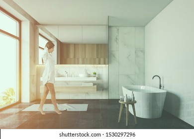 Beautiful young woman in nightgown walking in luxury bathroom interior with marble walls, comfortable tub, double sink with mirror and large window. Toned image double exposure