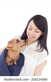 beautiful young woman with Norfolk terrier dog in carry bag, isolated on white background