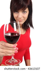 Beautiful young woman offering glass of wine in front of white background