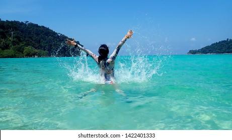 Beautiful young woman on the beach splashing water