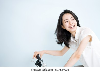 Beautiful young woman on bicycle against light blue background.