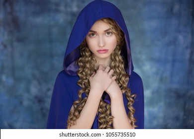 Beautiful young woman on a blue background in a raincoat and hood. Medieval costume of fantasy. The heroine of the fairy tale, the princess, the duchess.