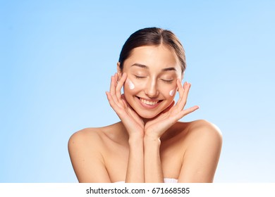 Beautiful young woman on a blue background applies cosmetic face cream.